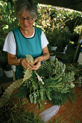 An expert at haku lei and ikebana (Japanese flower arranging), Maryanne Lambert turns her talents to crafting wreaths for the Hui's Christmas fund raiser.