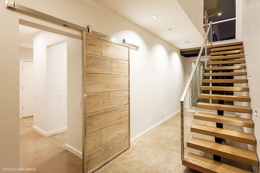 A stairway leads up to the great room; to its left, a wood panel slides to conceal the home's utility areas, its wood repurposed from an old barn on the property.