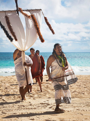 A modern-day procession in Waimanalo, O'ahu, signals the arrival of Makahiki. The wooden staff, with its crosspiece draped in white kapa and feather lei, represents the god Lono.